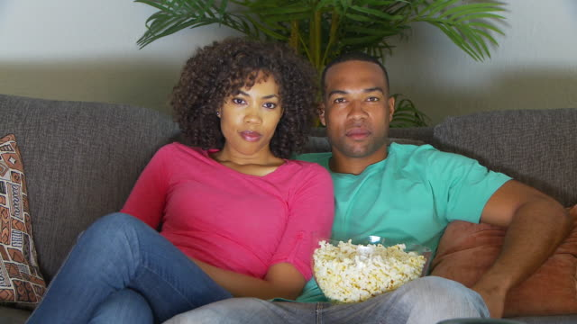 couple watching movie on couch while eating popcorn - freundin stock-videos und b-roll-filmmaterial