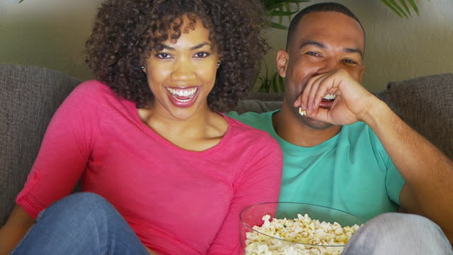Couple watching movie on couch while eating popcorn