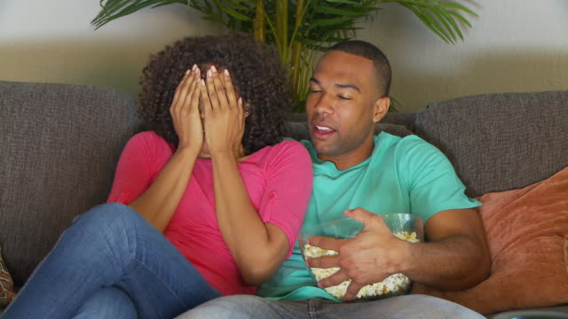 Couple watching scary movie on couch