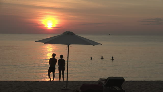 vídeos de stock, filmes e b-roll de a couple watching sunset at sea - chapéu de sol