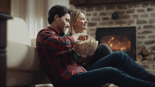 couple watching television and eating popcorn - watching tv stock videos & royalty-free footage