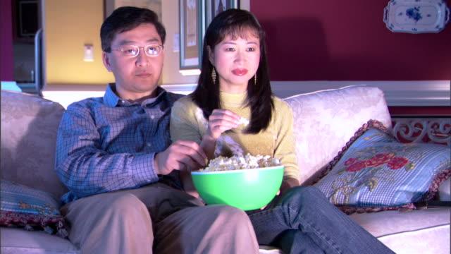 couple watching television and eating popcorn - andere clips dieser aufnahmen anzeigen 1282 stock-videos und b-roll-filmmaterial
