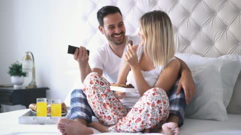 paar vor dem fernseher im schlafzimmer. - überbelichtet stock-videos und b-roll-filmmaterial