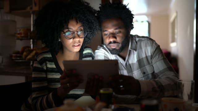 vídeos de stock, filmes e b-roll de casal assistindo vídeo em tablet digital em casa - distante