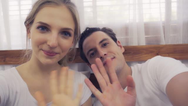 coppia che agita le mani e guarda la fotocamera - salutarsi video stock e b–roll