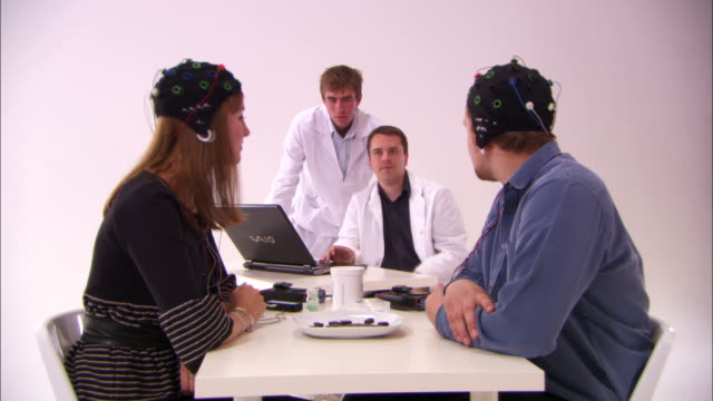 a couple wear electrodes on their heads and eat chocolate while research scientists observe. - scientific experiment stock videos & royalty-free footage