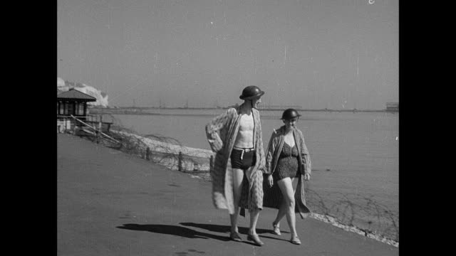 montage a couple wearing bathing suits and helmets walking along the beach as a naval convoy passes through the channel and an warplane flies overhead / dover, england, united kingdom - england stock-videos und b-roll-filmmaterial