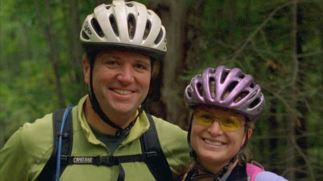 cu, couple wearing bicycle helmets smiling and talking standing in forest, carrabassett valley, maine, usa - cycling helmet stock videos & royalty-free footage