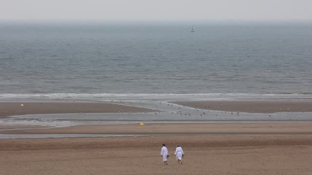 couple wearing white bathrobes walks on the beach towards the north sea on july 13 in ostend, belgium. the seaside resort of ostend is located on the... - bathrobe stock videos & royalty-free footage