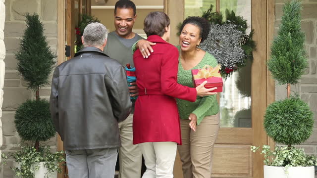 couple welcoming friends to their home for Christmas