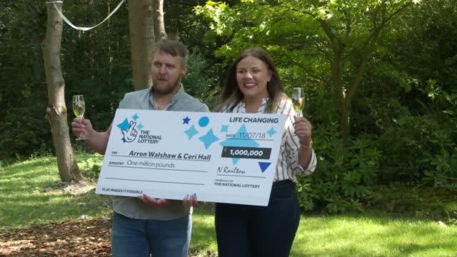 vídeos de stock, filmes e b-roll de couple win 1 million pounds on the lottery after woman let them queue jump england ext arron walshaw and ceri spraying champagne as posing walshaw... - jogo da sorte