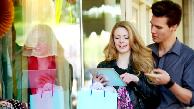 Couple window shopping with a tablet
