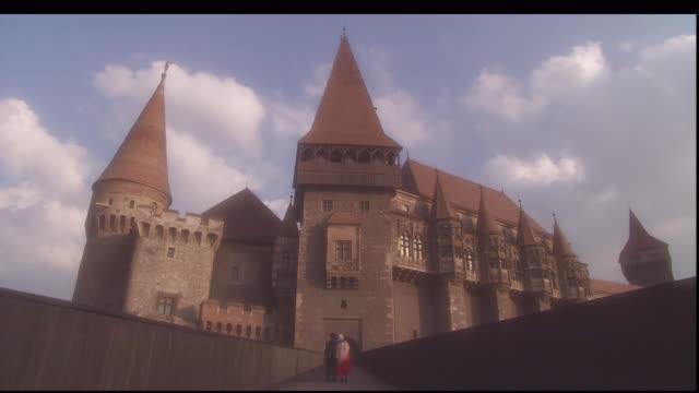 a couple with an infant walks away from hunedoara castle in romania. - siebenbürgen stock-videos und b-roll-filmmaterial