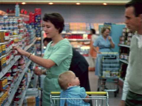 1960 couple with baby in shopping cart taking jars of baby food from shelves in grocery store