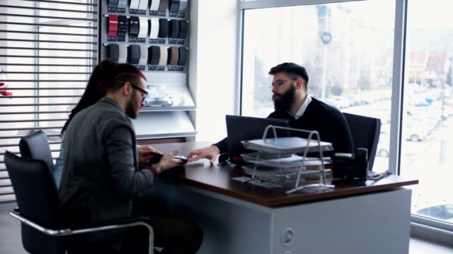 Couple with car salesperson discuss about car material