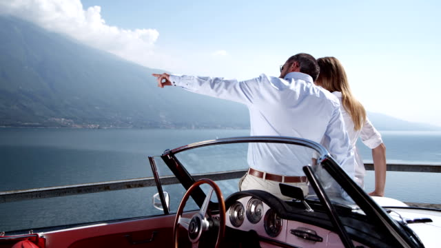 stockvideo's en b-roll-footage met couple with convertible watching over a lake - overvloed