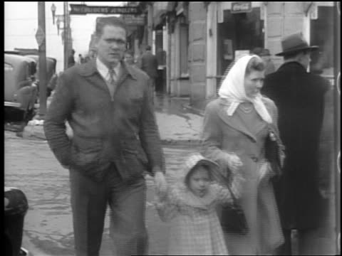 b/w 1944 couple with daughter holding hands + crossing street in winter / lexington, nc / docu. - winter点の映像素材/bロール