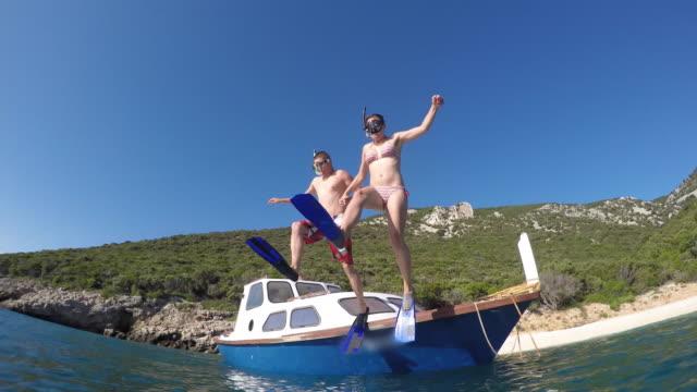 POV paar met duiken maskers springen uit een boot in de zee