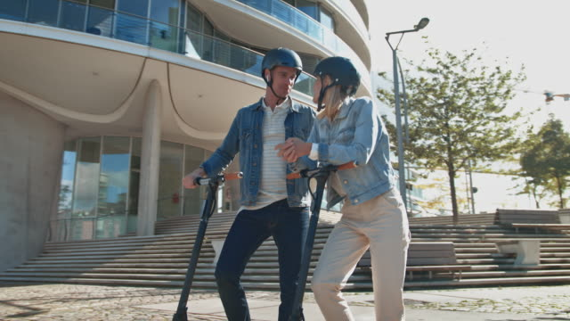 couple with electric kick scooters talking in city - helmet stock videos & royalty-free footage