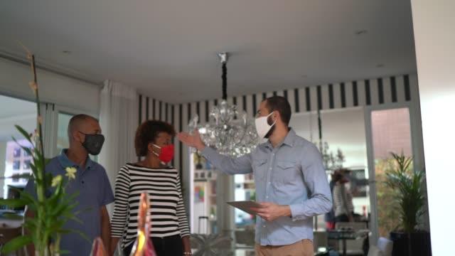 vídeos y material grabado en eventos de stock de pareja con mascarilla visitando una casa a la venta - propiedad inmobiliaria