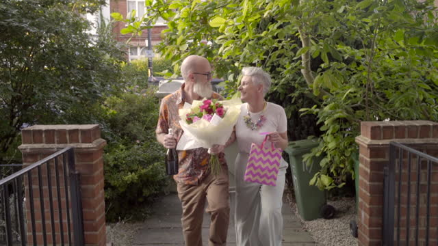 a couple with flowers arrive at a house. - grey hair stock videos & royalty-free footage