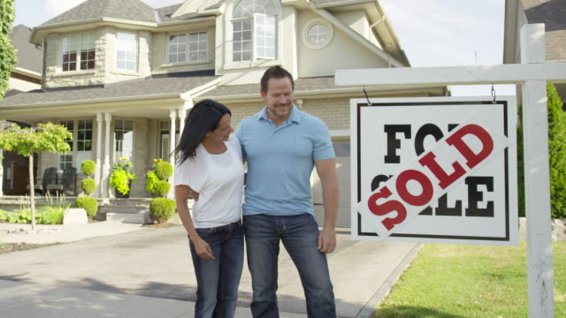"""couple with """"for sale, sold"""" real estate sign - selling stock videos and b-roll footage"""