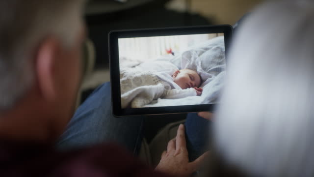 couple with grandchild photograph on tablet pc - using digital tablet stock videos & royalty-free footage
