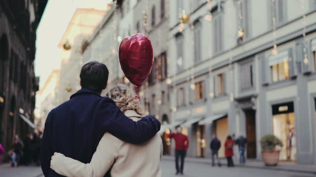 couple with heart shaped balloon walking in old town, florence, italy - city break stock videos & royalty-free footage
