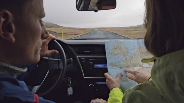 ms couple with map driving car on road through remote landscape,iceland - wife stock videos & royalty-free footage