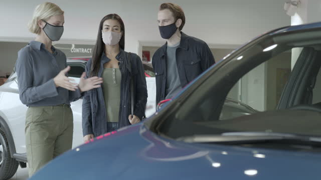 vídeos de stock e filmes b-roll de couple with saleswoman looking at electric car in automotive showroom wearing protective face mask - aluguer de automóveis