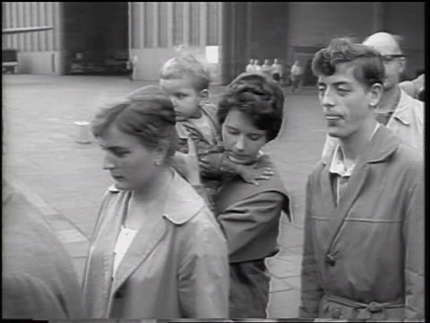 b/w 1961 couple with small child in line outdoors / east german refugees / beginning of berlin wall - 1961 stock-videos und b-roll-filmmaterial