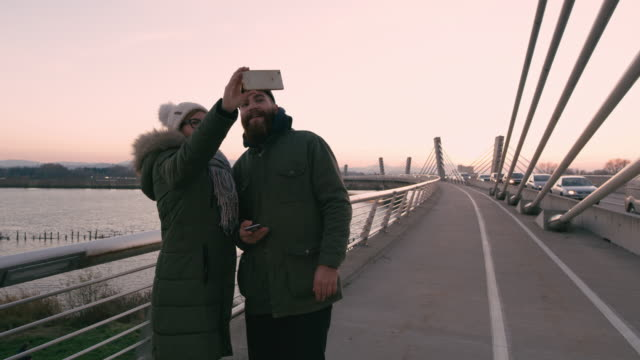 ms couple with smart phone taking selfie on bridge - coppia di adulti di mezza età video stock e b–roll