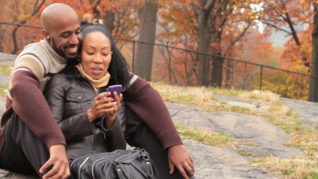 ms pan slo mo couple with smartphone listening to music in central park / new york city, new york, usa. - autumn stock videos & royalty-free footage