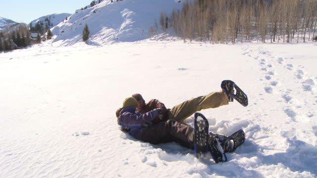 couple with snow shoes playing in the snow / ketchum, idaho, united states - teasing stock videos & royalty-free footage
