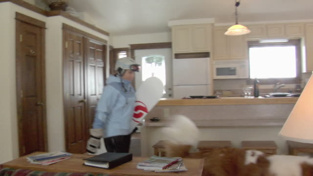 vidéos et rushes de ms, pan, couple with snowboards arriving to mountain cabin, whitefish, montana, usa - sport d'hiver