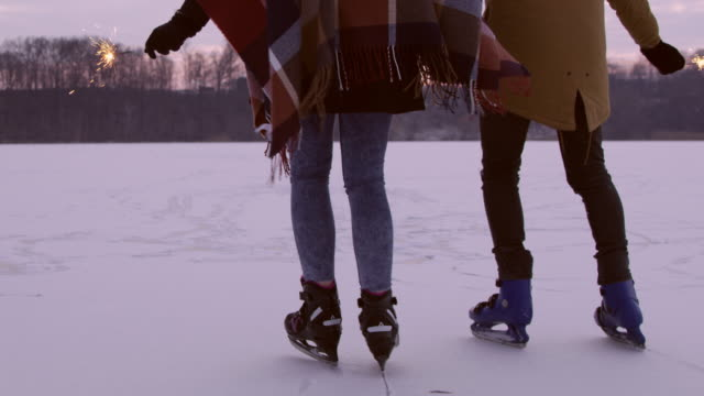 4k couple with sparklers holding hands ice skating on frozen lake, slow motion - ice skating stock videos & royalty-free footage