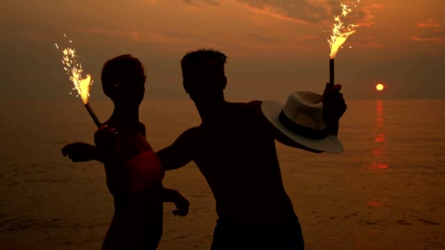 slo mo couple with sparklers on the beach - sunglasses stock videos & royalty-free footage