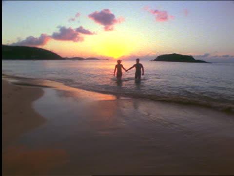 vídeos de stock e filmes b-roll de couple with swimsuits holding hands running from surf to beach at sunset / st. john, us virgin islands - perto