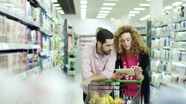 vídeos de stock, filmes e b-roll de casal com tablet compras no supermercado - ficando de pé