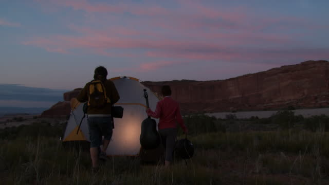 couple with tent camping outdoors at dusk - young men stock videos & royalty-free footage