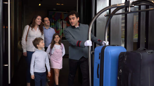couple with their two children walking out of luxury hotel following bellhop pushing a luggage cart ready to leave - hotel stock videos & royalty-free footage