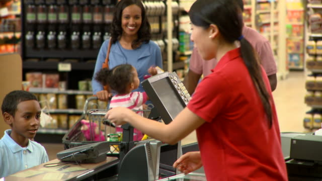 MS TU Couple with two kids (2-9) paying for groceries at supermarket check out, Richmond, Virginia, USA