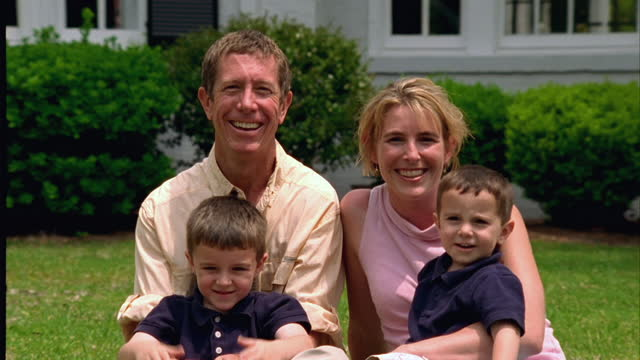 a couple with two sons poses in front of their home. - in front of stock videos & royalty-free footage