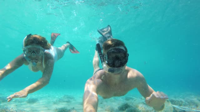 stockvideo's en b-roll-footage met ms couple met draagbare camera onderwater snorkelen in de blauwe oceaan - halfgekleed