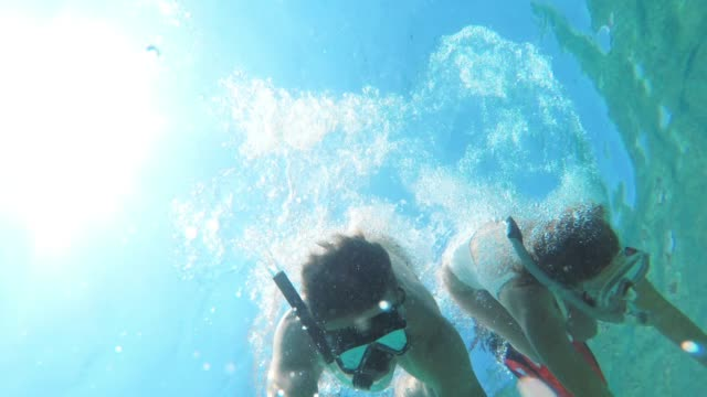 MS Couple with wearable camera snorkeling underwater in blue ocean