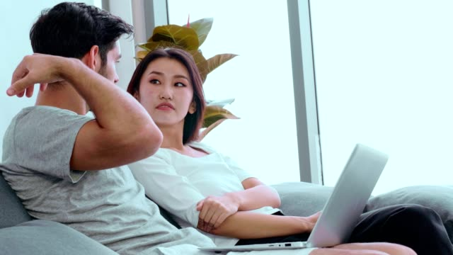 couple working from home using phone and laptop - hot desking stock videos & royalty-free footage