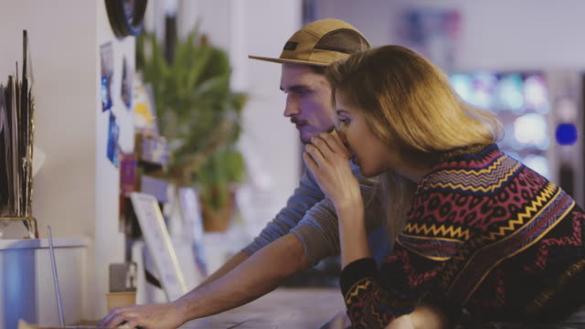 DS Couple working late on laptop in startup office