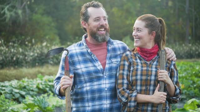 vidéos et rushes de couple travaillant sur la ferme familiale, sourire à la caméra, parler - 40 44 ans
