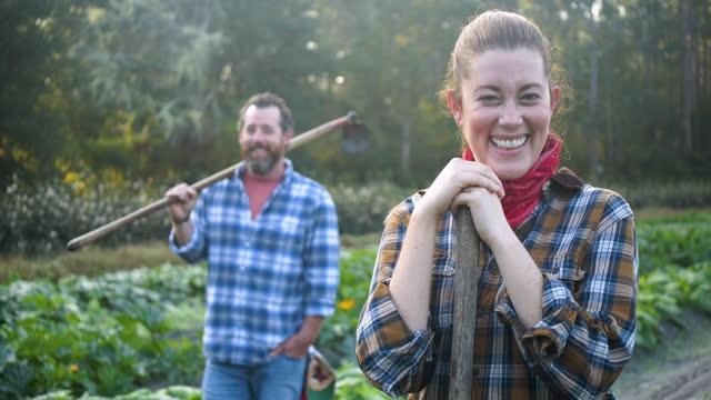 vidéos et rushes de couple travaillant sur la ferme familiale, parlant, sourit à la caméra - 40 44 ans