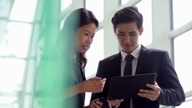 MS couple working together on a digital tablet in an office.
